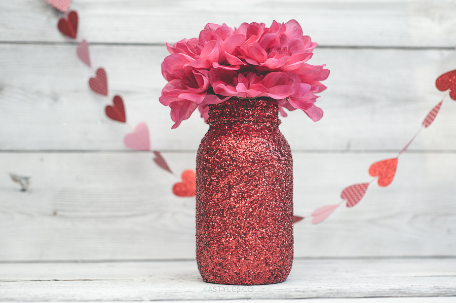 Red glitter Valentine's Day mason jar vase for decor or gifts.